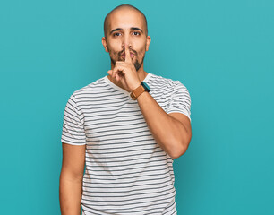 Fototapeta Hispanic adult man wearing casual clothes asking to be quiet with finger on lips. silence and secret concept. obraz