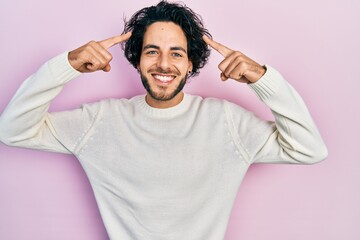 Handsome hispanic man wearing casual white sweater smiling pointing to head with both hands finger, great idea or thought, good memory Wall mural