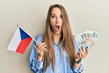 Young blonde woman holding czech republic flag and koruna banknotes afraid and shocked with surprise and amazed expression, fear and excited face.