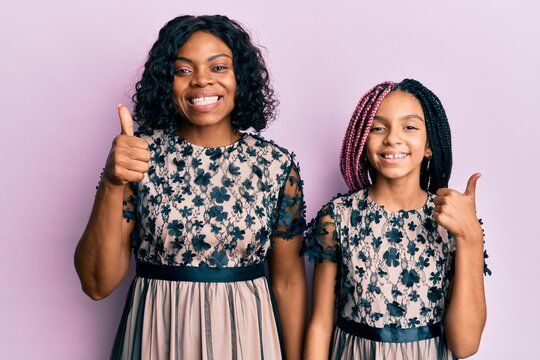 Beautiful african american mother and daughter wearing sexy party dress smiling happy and positive, thumb up doing excellent and approval sign