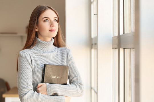 Young woman with Bible at home
