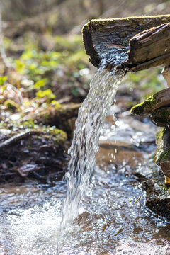 An ancient wellspring with clean drinking water in the forest. A pure, fresh, drinking water from natural source. The spring is equipped with a wooden trough for water flow