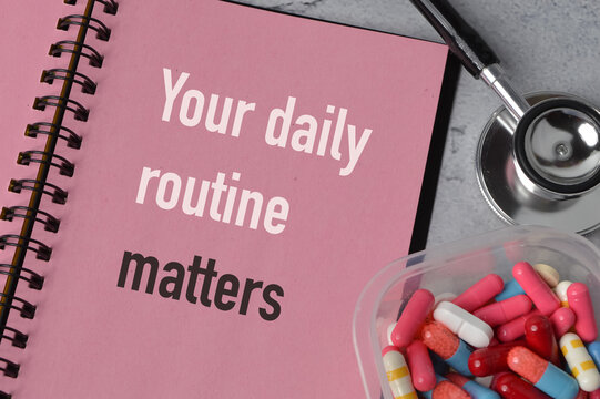 Top view of stethoscope, pill capsules and notebook written with YOUR DAILY ROUTINE MATTERS.