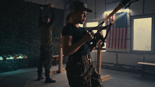Female soldier doing TRX lunge near squadmate