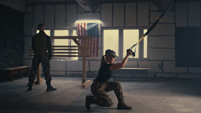 Sweaty female soldier exercising in gym