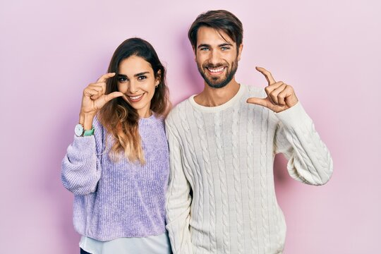 Young hispanic couple wearing casual clothes smiling and confident gesturing with hand doing small size sign with fingers looking and the camera. measure concept.