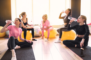 Group of athletic women having fun on a break during sports training, drink fresh water