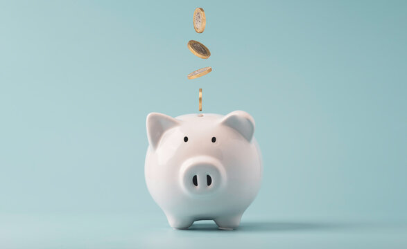 Coins falling to white piggy saving ,  Financial and money deposit concept.