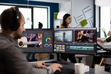 Video maker listening music at headphones editing movie using post production software working in...