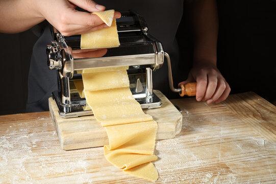 Pasta maker machine, woman's hands make fresh pasta sheets for tagliatelle, ravioli or lasagna.