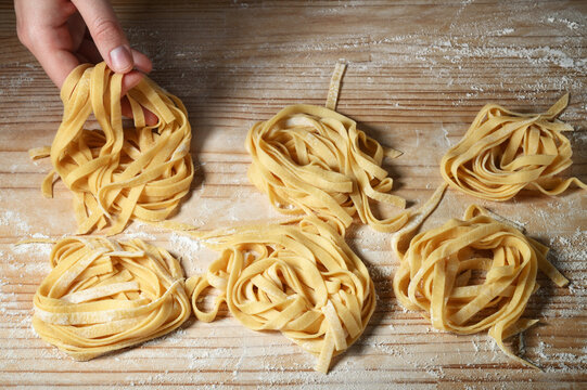 Woman's hands make tagliatelle or fettuccine on pastry board. Fresh egg pasta nests.