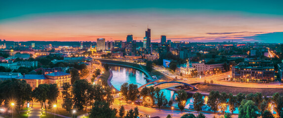 Fototapeta Vilnius, Lithuania, Europe. Sunset Cityscape. Modern Office Buildings Skyscrapers In Business District New City Center Shnipishkes In Night Illuminations. Panorama obraz