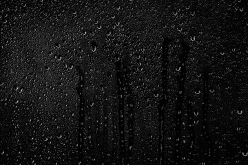 Obraz Drops of water flow down the surface of the clear glass on a black background. Texture for creativity. - fototapety do salonu