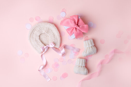 Beautiful composition with baby booties shoes, bonnet and gift box on pink background. Concept of baby shower party, pregnancy, mother day, first birthday holiday card, copy space, banner