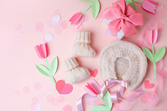 Bonnet and booties on a pink background. Handmade clothes for a newborn, decorative paper flowers. Newborn baby gift concept, mom's day, first birthday, first wardrobe, outfit