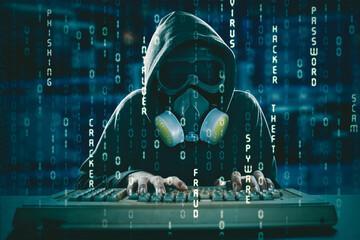 Hooded male hacker in gas mask using a computer - fototapety na wymiar