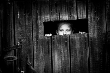 Fototapeta Little girl startled looks out of the shed through a small window. obraz