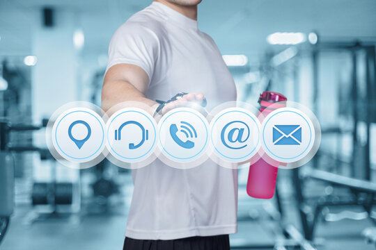 Fitness athlete clicks on the contact icons on the background of the gym.