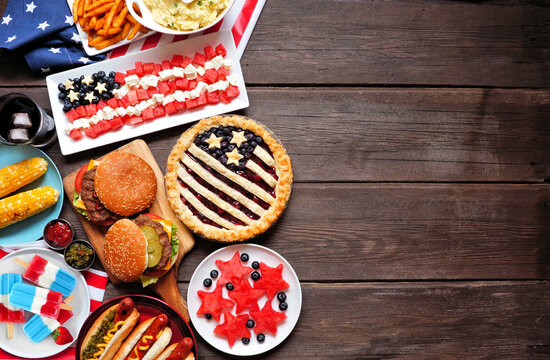 Fourth of July, patriotic, American themed food. Top view side border on a dark wood background. Copy space.
