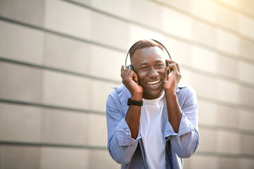 Positive black guy listening to new music playlist in headphones near brick wall outdoors, free...