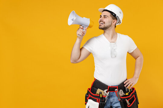 Young employee handyman man in protective helmet hardhat scream shout in megaphone aside isolated on yellow background studio. Instruments accessories renovation apartment room Repair home concept