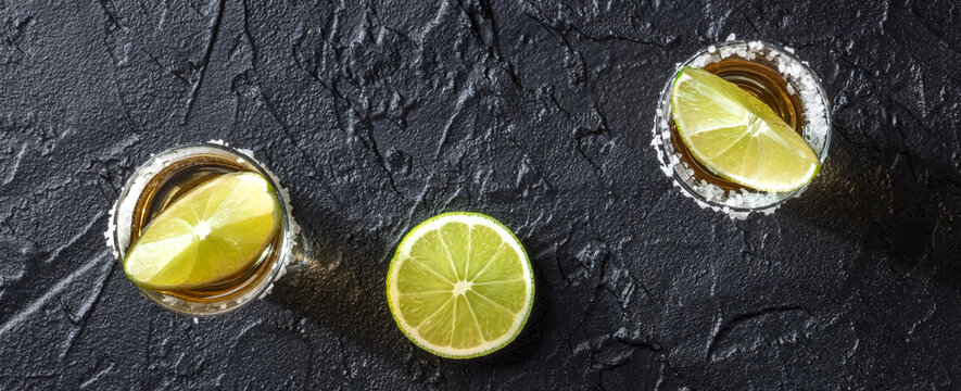 Tequila and lime panorama on a black background