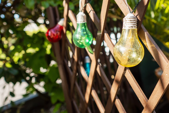 Colorful string bulbs hanging on a wooden fence in a back yard. Getting ready to party concept. Selective focus. Warm sunny day