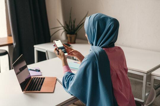 modern muslim woman in hijab in office room