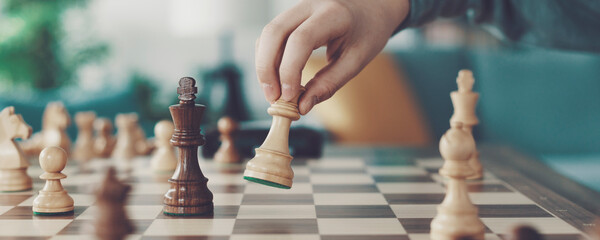 Fototapeta Boy playing chess and moving a piece obraz