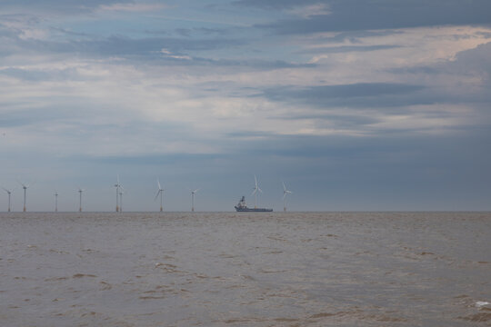 Turbines on the horizon with a shipping vessel
