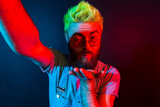 Romantic bearded hipster man with beard in denim overalls talking via web camera with girlfriend, expressing love, broadcasting live stream. Colorful neon light, indoor studio shot.