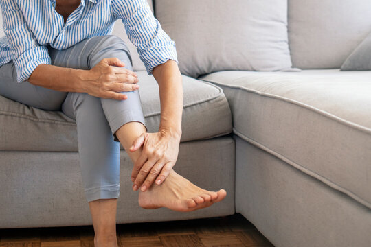 Closeup young woman feeling pain in her foot at home. Healthcare and medical concept. Tired and aching female feet after walking. Woman with feet intense pain sitting on a couch at home.