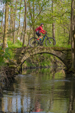 nice active senior woman riding her electric mountain bike in early spring along the little river Glems near Stuttgart, Baden-Wuerttemberg, Germany