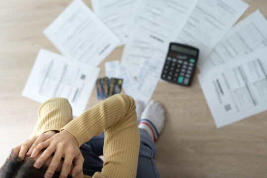Women stress about a lot of credit card debt and bills on the floor. The housewife has trouble calculating monthly expenses and the budget is not enough to pay off the debt