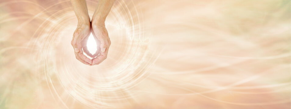 Healer sending Unconditional Love Healing Energy -  female cupped hands making an O shape with a bright light between against a pale golden vortex energy field flowing across and space for messages