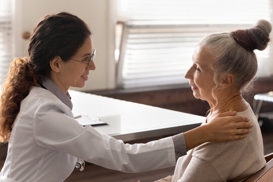 At doctor appointment. Elderly female patient visit family therapist feel support empathy caring attitude on consultation. Woman gp talk to mature lady client at examination room hold hand on shoulder