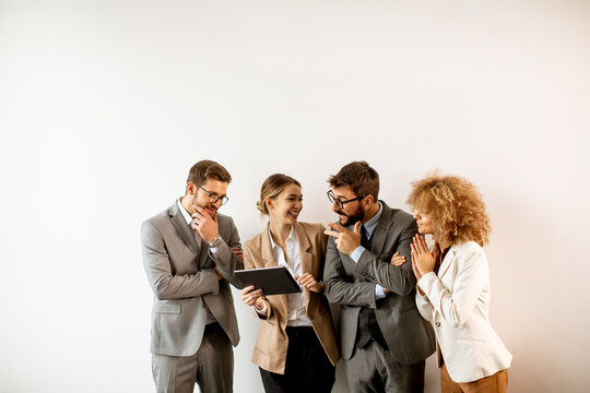Multiethnic business people using digital tablet while standing by the wall in the office