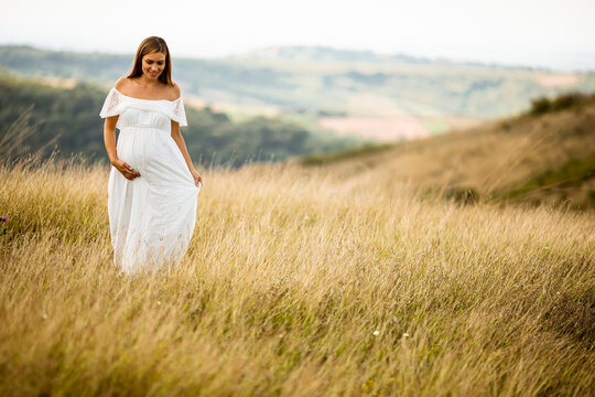Young pregnant woman at the field