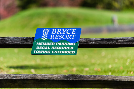 Basye, USA - October 7, 2020: Bryce ski resort parking lot with sign on wooden fence with member decal required and towing enforced for violators in countryside rural Virginia mountain town