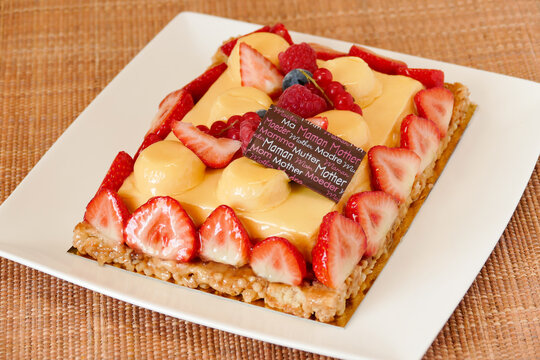 Motherday fruit tart on white plate, yellow cream with passion fruit flavor and red berries coulis on caramel crust