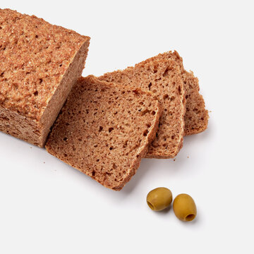 sliced rye bread on a white plate with  olives