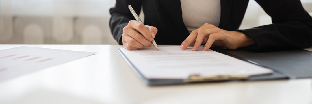 Businesswoman signing a document or application form in a folder