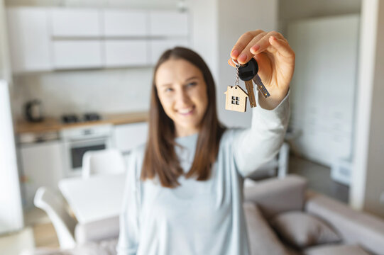 Selective focus on the key in hand of happy young woman, cheerful female moved in new house, rent apartment, bought own real estate, the key with keyring in shape of little house