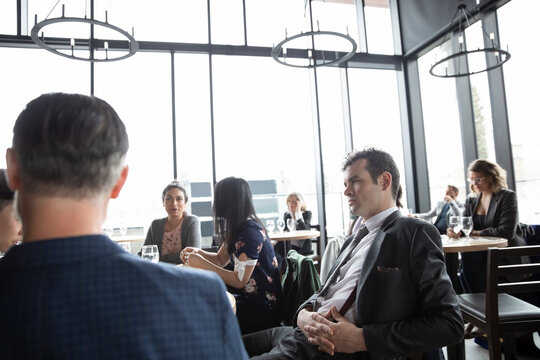 Businessman listening to colleagues at business lunch in restaurant