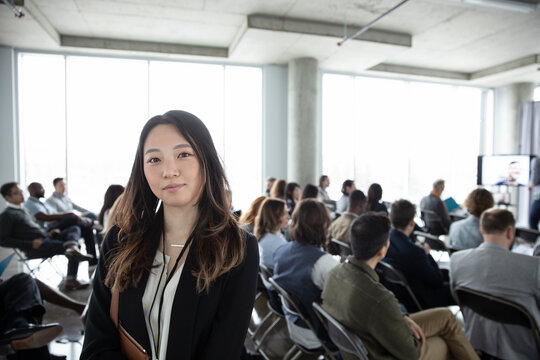 Portrait confident young businesswoman at business conference