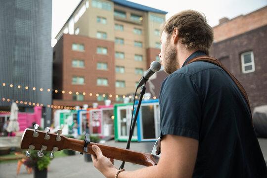 Male musician performing, playing guitar and singing at urban bazaar m