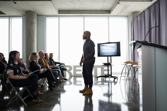 Creative businessman speaker leading conference presentation