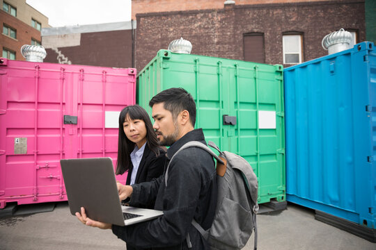 Real estate developers with laptop talking at urban bazaar marketplace