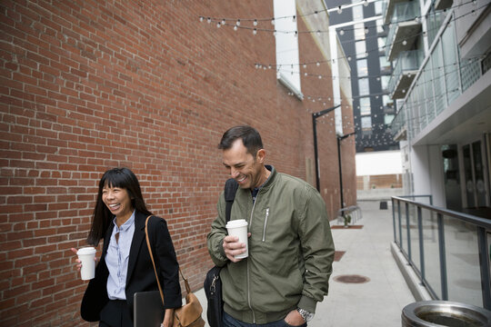 Business people with coffee walking in urban alley