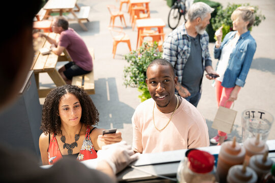 Couple paying with credit card at food truck